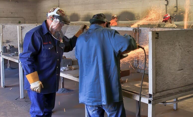 Man Showing To Apprentice How To Weld
