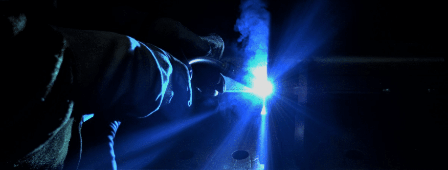 welding in the dark with blue flame and brown leather gloves