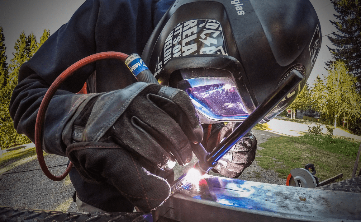 outside welding with black helmet and gloves